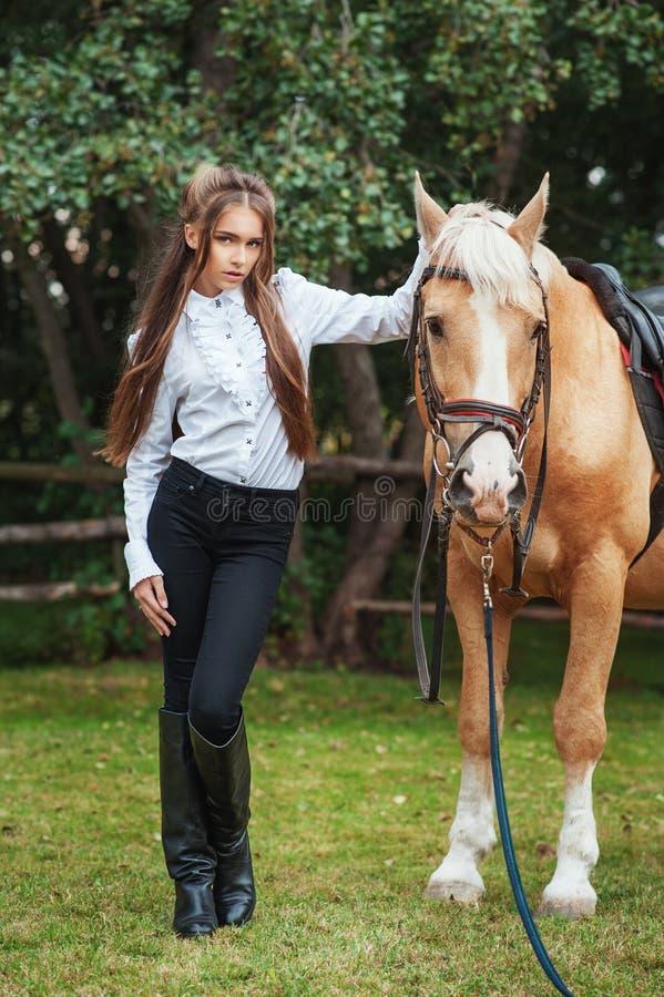 Moça bonita do retrato na camisa branca e em calças pretas com o cavalo seguinte do cabelo longo da beleza no woma elegante da  fotografia de stock royalty free