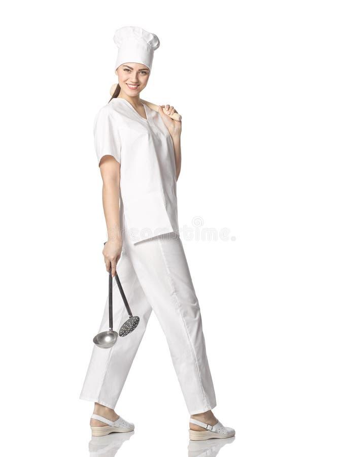 A moça bonita em um cozinheiro chefe veste-se com a vária ferramenta da cozinha fotos de stock royalty free