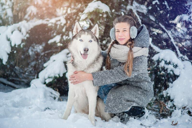 Moça bonita em um revestimento cinzento na floresta do inverno com cão de puxar trenós Siberian Símbolo do ano novo 2018 fotos de stock