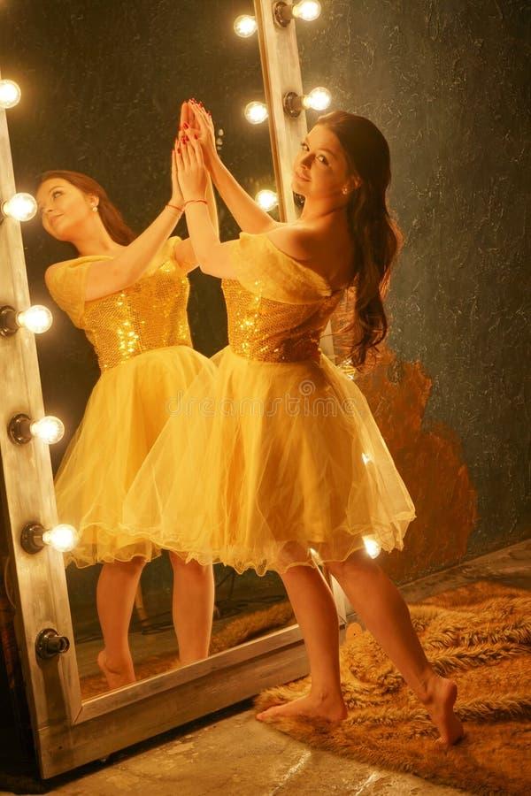 A moça bonita em um vestido de noite do ouro está em um tapete da pele perto de um grande espelho em um quadro com luzes e olhare foto de stock