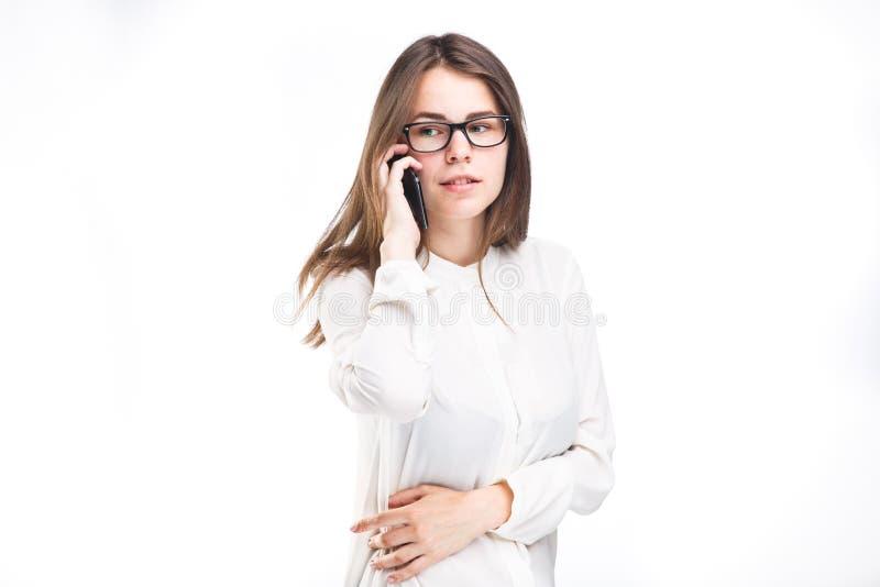 A moça bonita em uma camisa branca no branco isolou o fundo que fala em um telefone celular Sorri o retrato ao fotos de stock