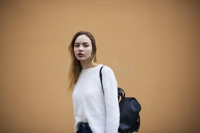 Moça bonita em uma camiseta leve em um fundo amarelo da parede fotos de stock