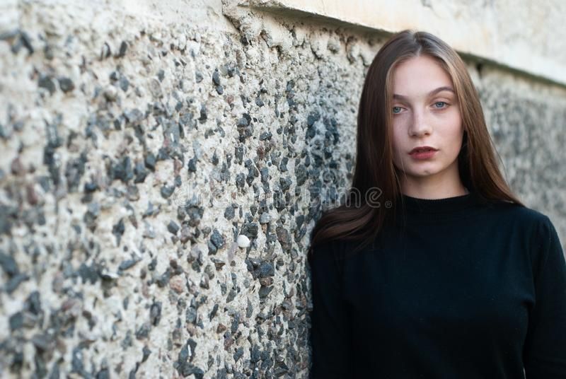 Moça bonita em uma camiseta preta da gola alta que levanta no muro de cimento imagem de stock