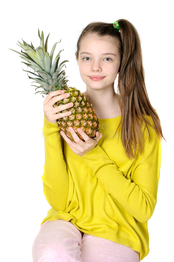 A moça bonita está guardando um grande abacaxi fotografia de stock royalty free
