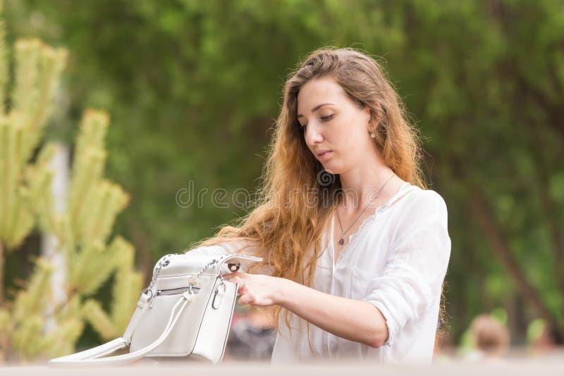 A moça bonita está investigando em sua bolsa no parque imagens de stock
