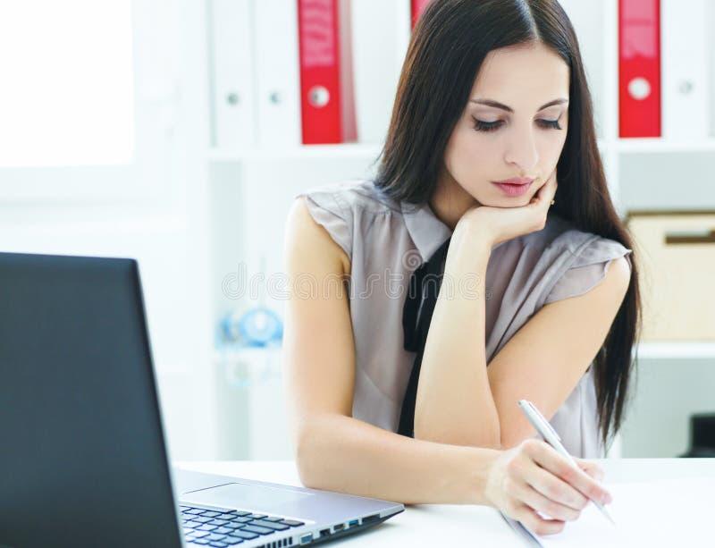 A moça bonita faz as anotações que sentam-se no escritório Negócio, mercado de troca, oferta de trabalho, pesquisa da analítica,  fotos de stock