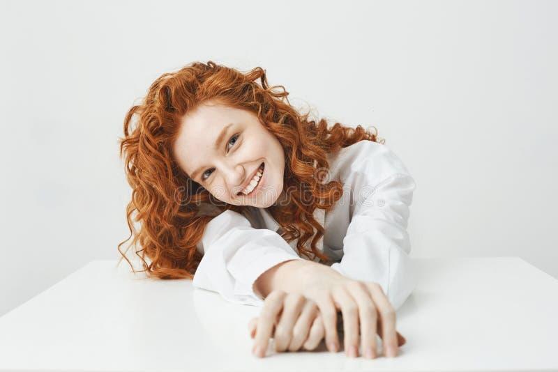 Moça bonita feliz com cabelo foxy que sorri olhando a câmera que senta-se na tabela sobre o fundo branco imagem de stock