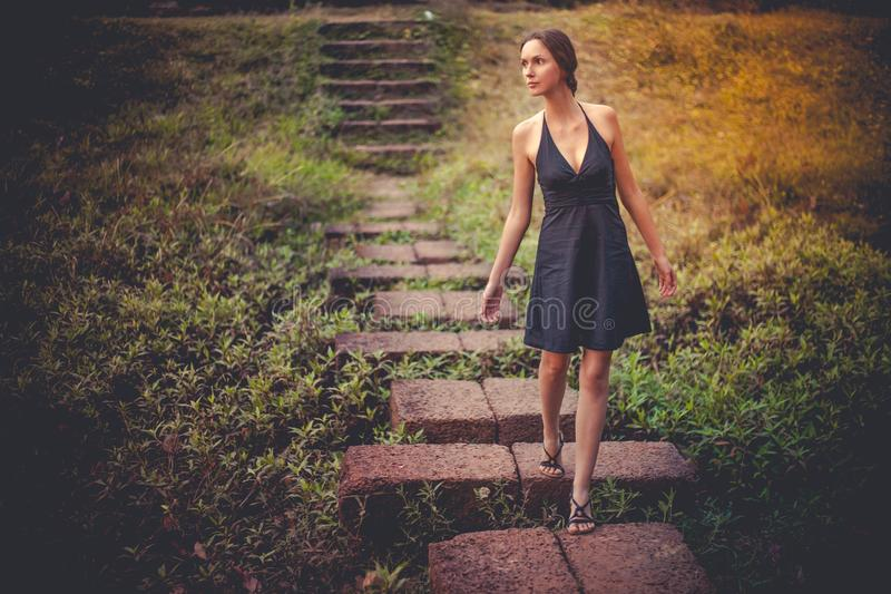 Moça bonita feliz que anda abaixo das escadas fotos de stock