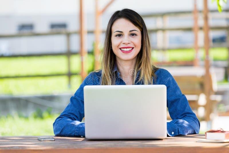 Moça bonita, feliz que usa o laptop fotos de stock royalty free