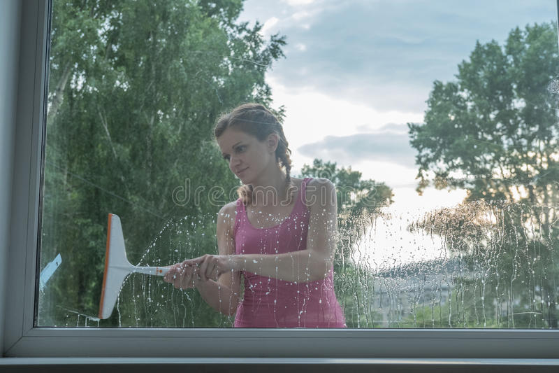 A moça bonita lava uma janela em uma casa do tijolo imagens de stock