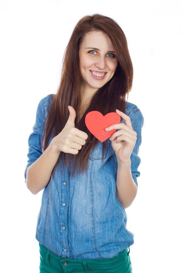 Moça bonita na camisa azul da sarja de Nimes que está em um fundo branco com um coração de papel vermelho nas mãos imagem de stock royalty free