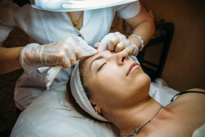 Moça bonita na sessão do procedimento com o esteticista, limpando e rejuvenescendo a pele facial Conceito da cosmetologia fotos de stock royalty free