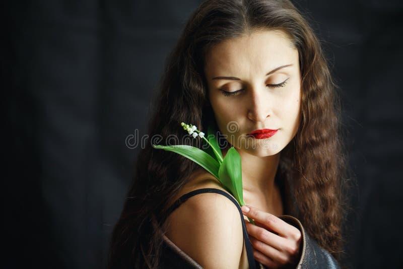 Moça bonita no casaco de cabedal que levanta no estúdio no fundo isolado preto Nas mãos das mulheres floresça fotografia de stock royalty free