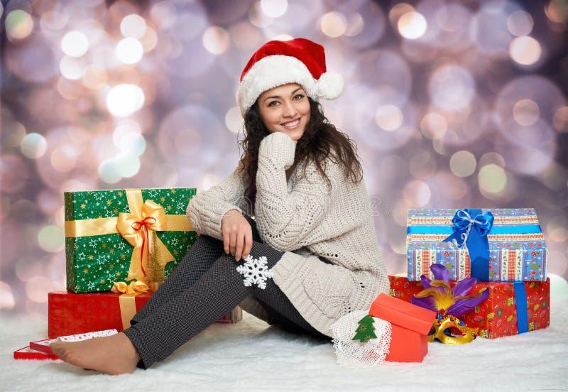 Moça bonita no chapéu de Santa com o brinquedo do floco de neve e as caixas de presente grandes, fundo colorido do bokeh fotos de stock royalty free