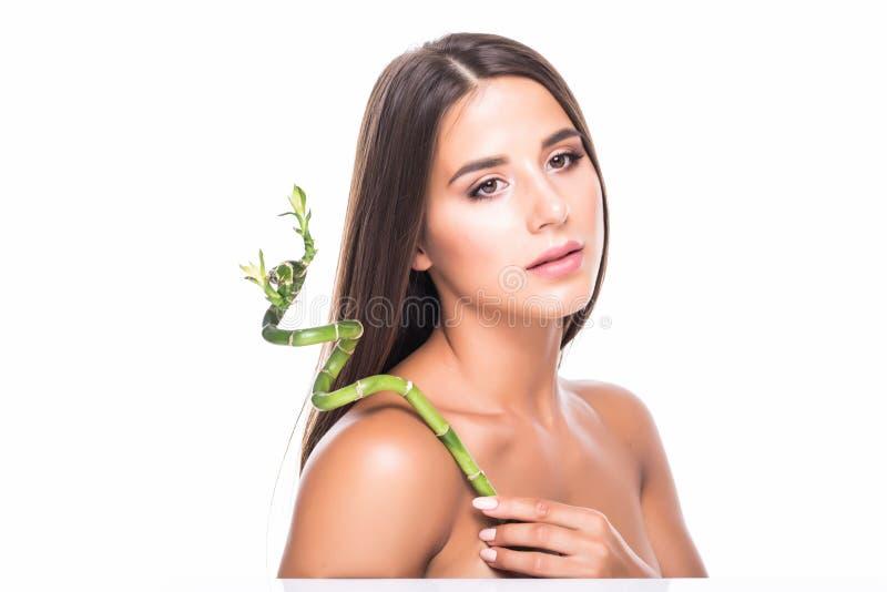 A moça bonita no estúdio em um fundo branco guarda uma folha tropical verde nas mãos e cobre uma parte de sua cara fotografia de stock