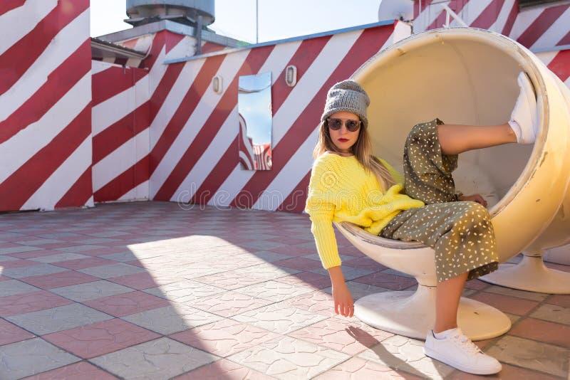 A moça bonita no moderno veste-se, óculos de sol, chapéu que descansa em uma cadeira redonda imagem de stock royalty free