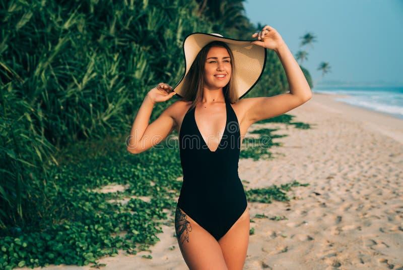 A moça bonita no roupa de banho elegante e no chapéu leve à moda com borda larga coloca estar de sorriso na praia foto de stock royalty free