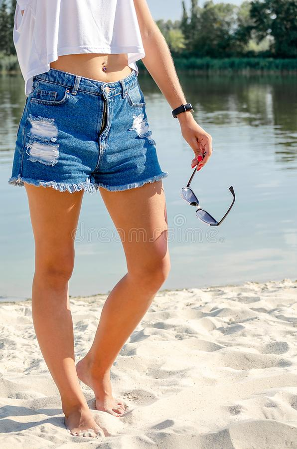 A moça bonita no short da sarja de Nimes está na praia foto de stock royalty free