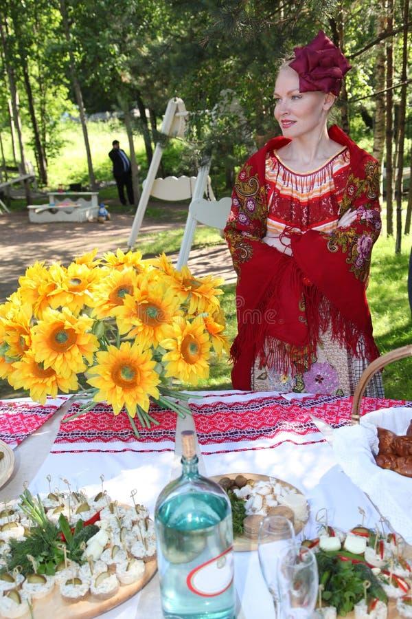 A moça bonita no traje ucraniano nacional apresenta a bebida alcoólica nacional foto de stock
