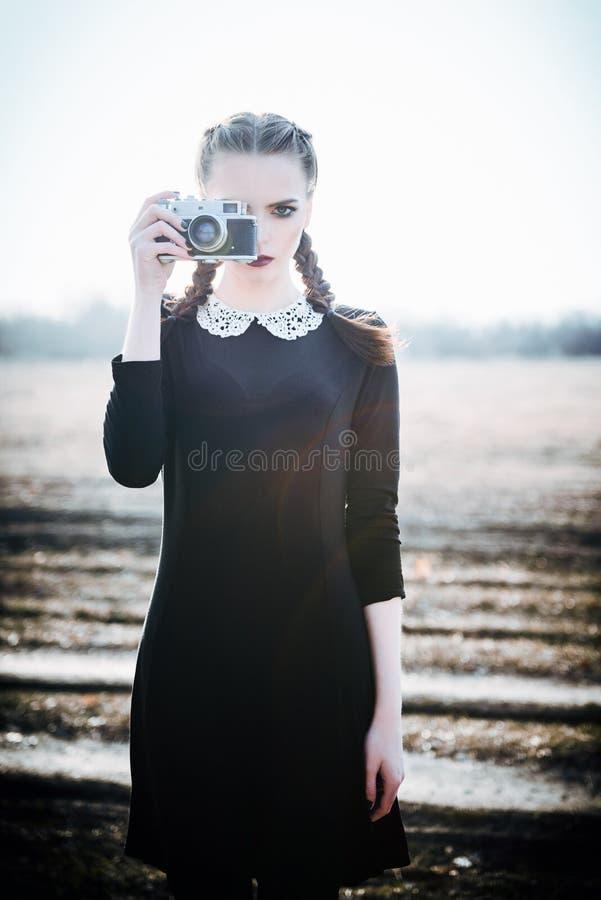 Moça bonita no vestido preto que toma imagens na câmera do filme do vintage Retrato ao ar livre imagem de stock royalty free