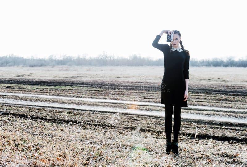 Moça bonita no vestido preto que toma imagens pela câmera do filme do vintage Retrato exterior do comprimento completo imagem de stock