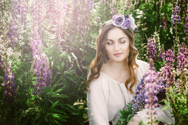 Moça bonita no vestido ultravioleta e branco que guarda um ramalhete do lupine no por do sol no campo O conceito da natureza e fotografia de stock royalty free