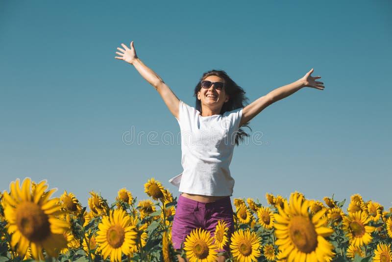 A moça bonita nos óculos de sol está nos girassóis com mãos acima e sorriso foto de stock