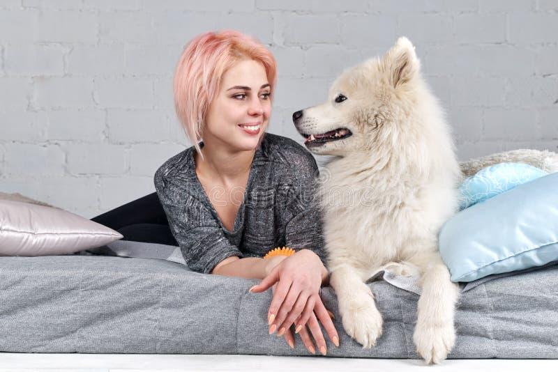 A moça bonita olha nos olhos de seu melhor amigo o cão foto de stock