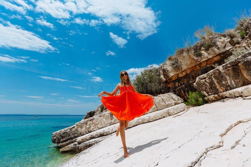 Moça bonita pelo mar Mulher em um vestido vermelho na praia Férias do beira-mar Terreno rochoso foto de stock royalty free