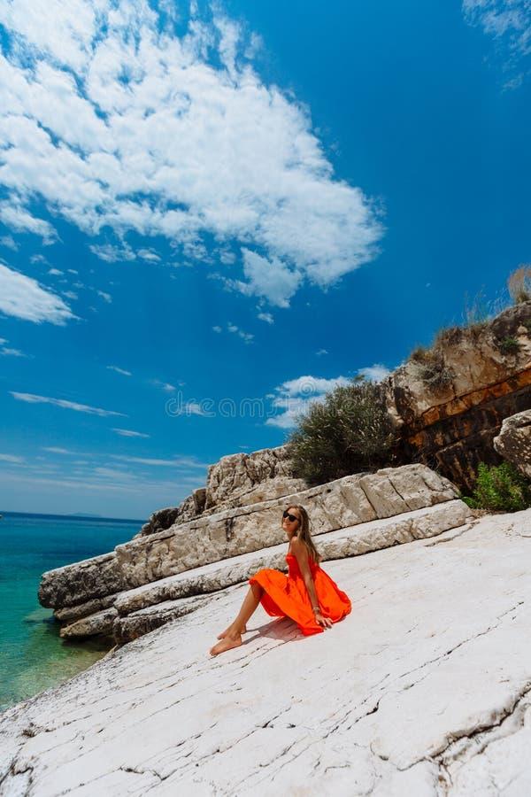 Moça bonita pelo mar Mulher em um vestido vermelho na praia Férias do beira-mar Terreno rochoso foto de stock