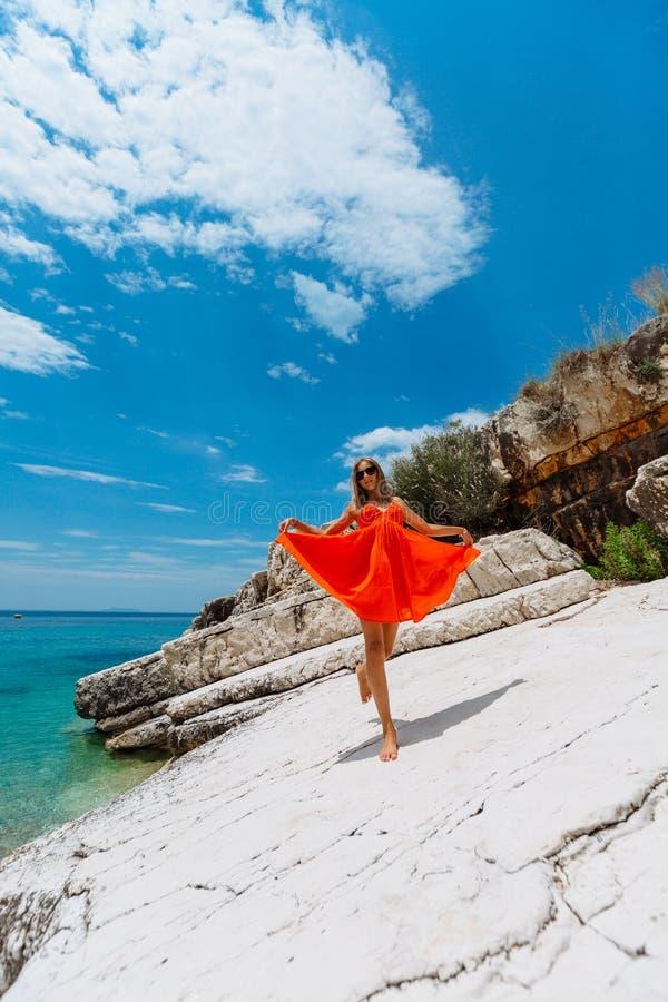 Moça bonita pelo mar Mulher em um vestido vermelho na praia Férias do beira-mar Terreno rochoso imagem de stock