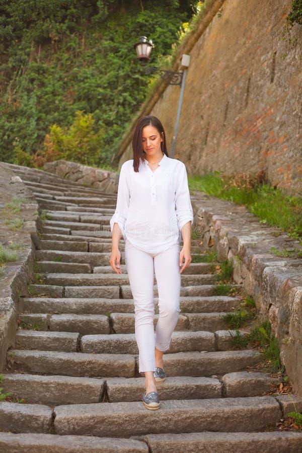 Moça bonita que anda abaixo das escadas de pedra fotografia de stock