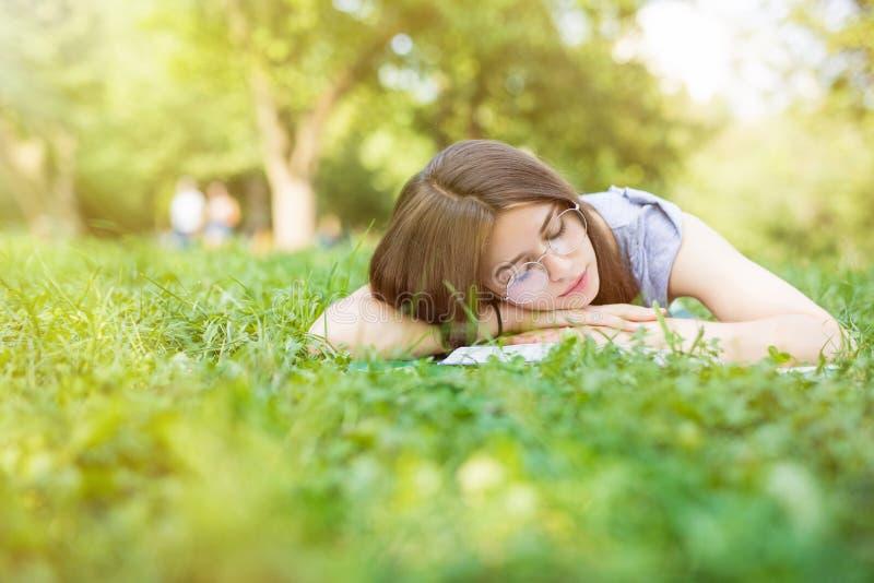 Moça bonita que encontra-se no caído no parque Sono de sorriso da mulher do estudante no livro em estações da floresta da queda,  fotografia de stock royalty free