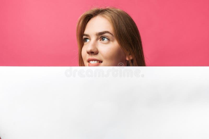 Moça bonita que espreita para fora da parede de trás do Livro Branco, no fundo cor-de-rosa fotografia de stock