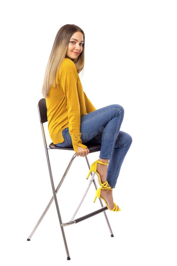Moça bonita que levanta em uma cadeira sobre o fundo branco fotos de stock royalty free