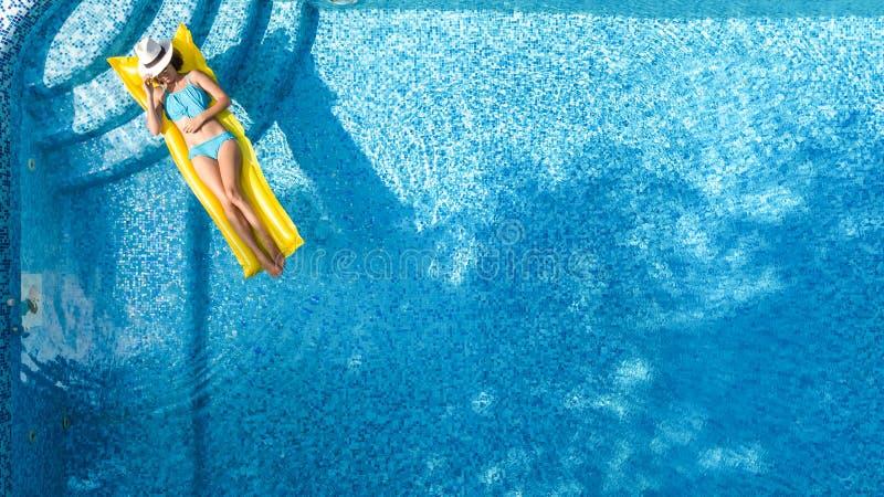 A moça bonita que relaxa na piscina, nadadas no colchão inflável e tem o divertimento na água em férias em família imagens de stock royalty free