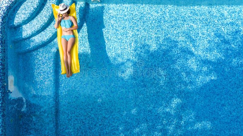 A moça bonita que relaxa na piscina, nadadas no colchão inflável e tem o divertimento na água em férias em família, vista aérea fotos de stock