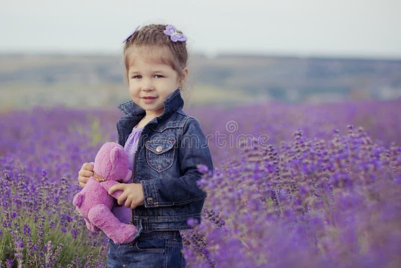 Moça bonita que senta-se no campo da alfazema no barqueiro agradável do chapéu com a flor roxa nela fotografia de stock