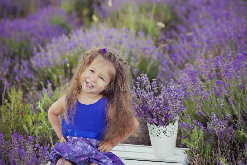 Moça bonita que senta-se no campo da alfazema no barqueiro agradável do chapéu com a flor roxa nela foto de stock
