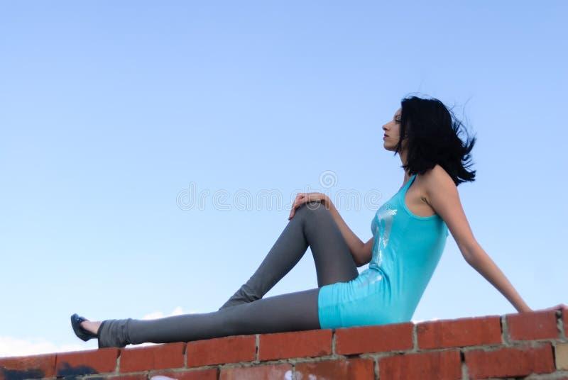 Moça bonita que senta-se no telhado fotografia de stock royalty free