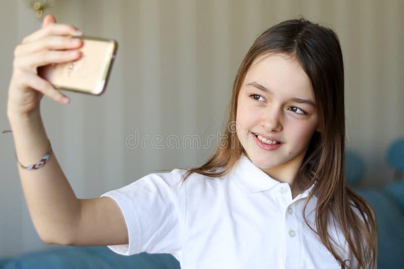 Moça bonita que sorri e que toma o selfie em casa imagem de stock royalty free