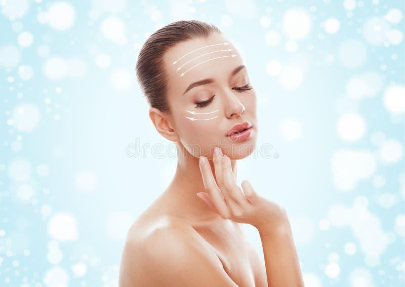 Moça bonita que toca em sua cara no fundo e na neve azuis Conceito da cirurgia plástica, do restauro e do rejuvenescimento imagens de stock royalty free