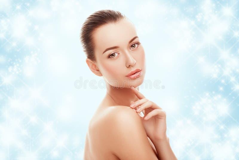 Moça bonita que toca em sua cara no fundo e na neve azuis Conceito da cirurgia plástica, do restauro e do rejuvenescimento foto de stock