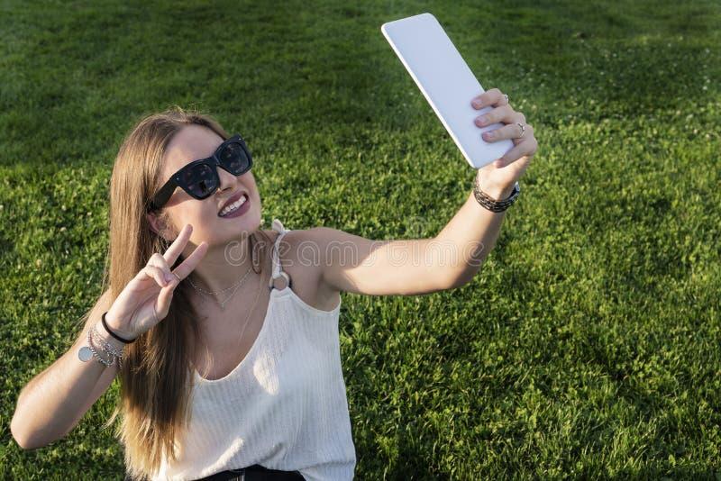 Moça bonita que toma um selfie no parque foto de stock