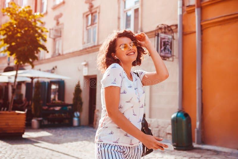 Moça bonita que usa o smartphone e escutando a música que anda na rua Dança da mulher e canto foto de stock
