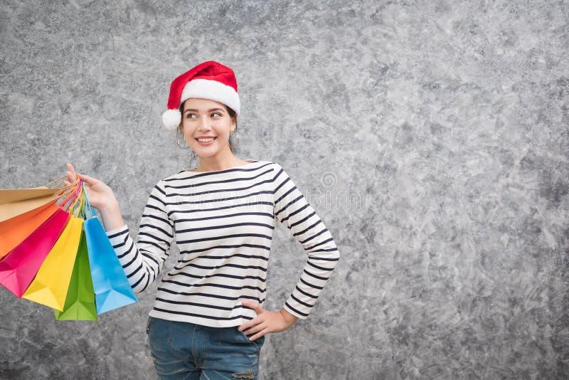 Moça bonita que veste um chapéu de Santa que guarda lotes dos sacos de compras foto de stock royalty free