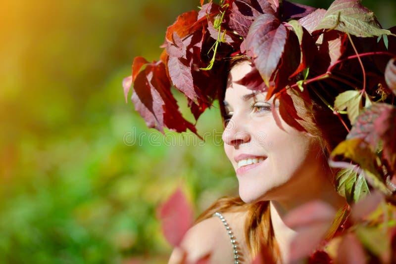 Moça bonita que veste uma grinalda das folhas de outono vermelhas e verdes que sorriem e que olham ao lado em um fundo verde imagens de stock royalty free