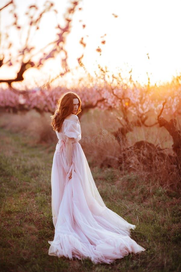 Moça bonita sob a árvore cor-de-rosa de florescência fotografia de stock