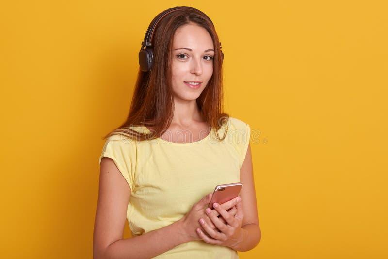 A moça bonita vestiu a música de escuta branca da camisa ocasional de t através dos fones de ouvido no fundo do estúdio, guardand fotografia de stock