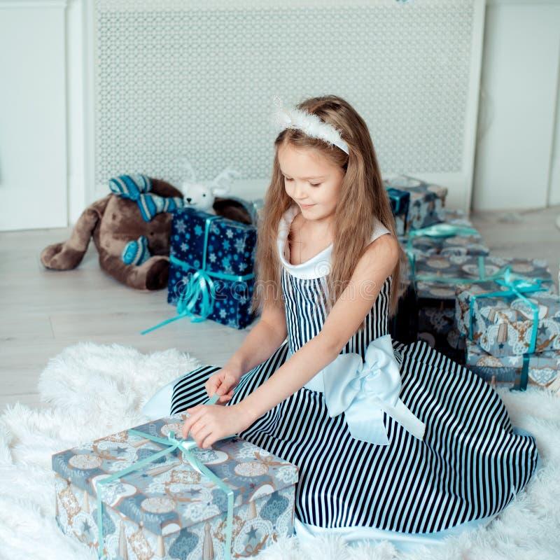 A moça bonito abre presentes na sala da decoração do Natal imagens de stock royalty free
